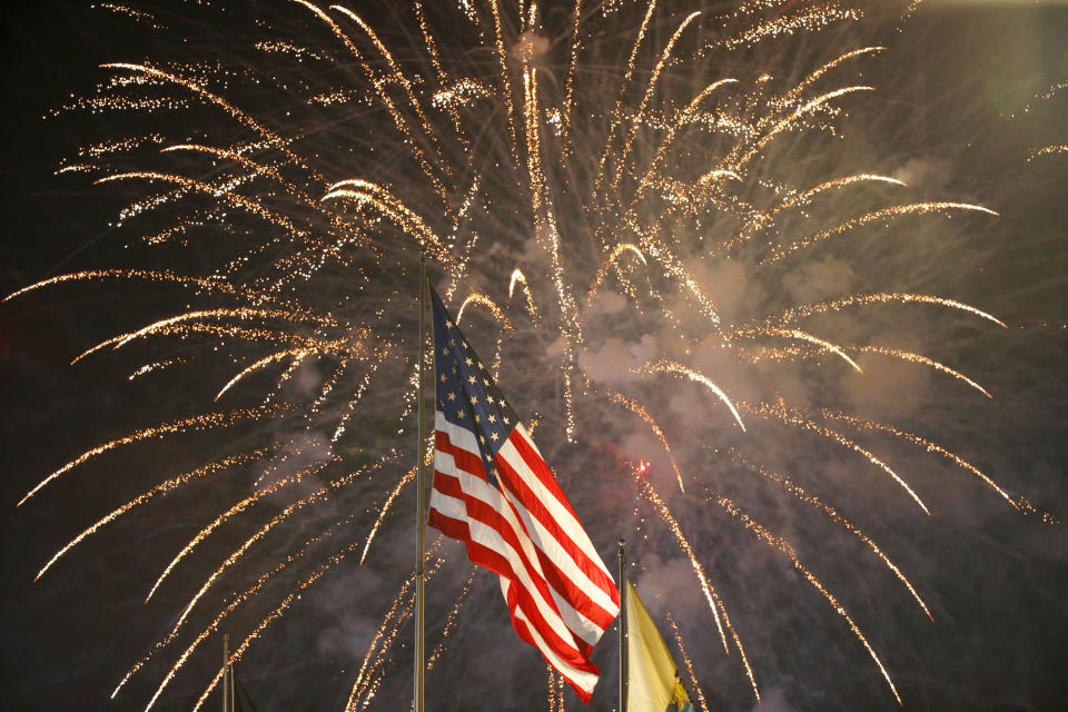 FILE - In this July 4, 2015, file photo, fireworks explode behind a United States flag during a Fourth of July celebration at State Fair Meadowlands in East Rutherford, N.J. With fewer professional celebrations on July 4, 2020, many Americans are bound to shoot off fireworks in backyards and at block parties. And they already are: Sales have been booming. (AP Photo/Julio Cortez, File)
