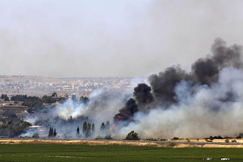 Smoke rises from a fire as a result of fighting in the the Syrian village of Quneitra near the border with Israel, as seen from an observatory near the Quneitra crossing, Thursday, June 6, 2013. Syrian rebels on Thursday captured a crossing point along a cease-fire line with Israel in the contested Golan Heights, a development that could deepen Israeli concerns over the growing role of Islamic radicals in the civil war near its northern frontier.(AP Photo/Sebastian Scheiner)