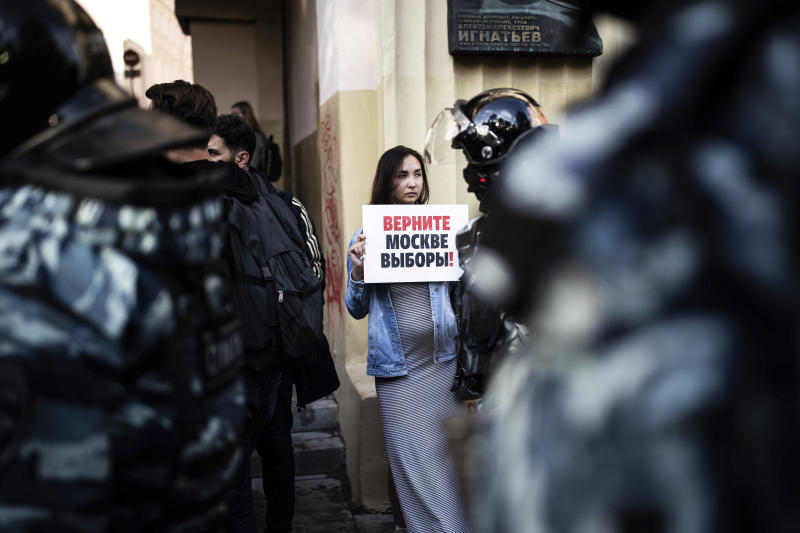 """A woman holds a poster reading """"Give us back our elections in Moscow!"""" in front of police during a protest in Moscow, Russia, Saturday, Aug. 10, 2019. Some thousands of people rallied Saturday against the exclusion of some city council candidates from Moscow's upcoming election, turning out for one of the Russian capital's biggest political protests in years. After the rally, which was officially sanctioned, hundreds of participants streamed to an area near the presidential administration building to continue with an unauthorized demonstration. (Evgeny Feldman, Meduza via AP)"""