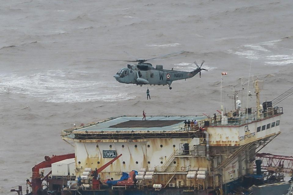 <p>Stranded workers from a barge, which had gone adrift amidst heavy rain and strong winds due to Cyclone Tauktae, being airlifted by naval personnel </p> (INDIAN NAVY/AFP via Getty Images)
