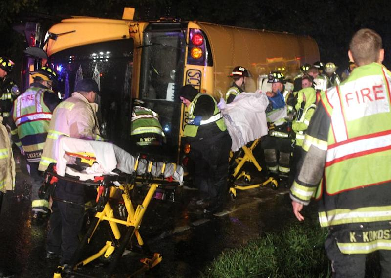 A victim is wheeled to an ambulance after a bus overturned on Howell School Road at the intersection with Summit Bridge Road after colliding with a carcarrier truck, reported about 10:00 p.m. Thursday evening, Oct. 10, 2013. State police Cpl. John Day says about 40 young adults, ages 18 to 22, were on the bus at the time. (AP Photo/The News Journal, William Bretzger)