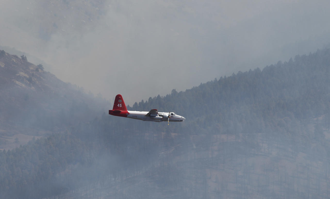 A slurry bomber makes its way toward a ridge through heavy smoke in the Lower North Fork Wildfire burning in the foothills community of Conifer, Colo., southwest of Denver on Tuesday, March 27, 2012. Firefighters are now able to actively battle the blaze on the ground that started on Monday and has already destroyed at least 16 homes in the rugged terrain. (AP Photo/David Zalubowski)