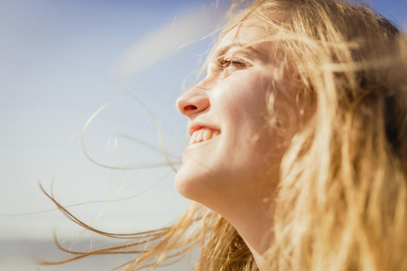 Close up carefree, smiling woman enjoying sunshine