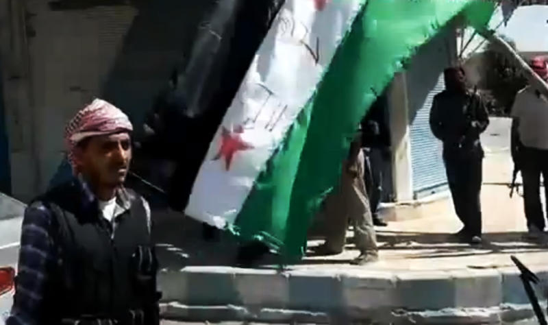 FILE - In this file image taken from video on Tuesday, Sept. 18, 2012 from the Ugarit News, which has been authenticated based on its contents and other AP reporting, Free Syrian Army soldiers seize the main square in the northern town of Raqqa, Syria. Since Raqqa fell under rebel control last week, opposition fighters have posted guards at government buildings to prevent looting, brought down the price of bread and opened a telephone hotline for residents to report security problems. Raqqa is shaping up as a test case for how rebels will administer their areas. (AP Photo/Ugarit News via AP video, File)