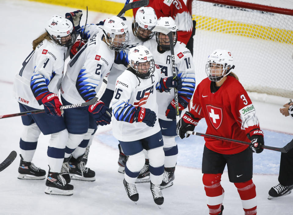 United States' Kendall Coyne Schofield (26) celebrates her goal as Switzerland's Sarah Forster skates away during the second period of an IIHF women's hockey championships game in Calgary, Alberta, Friday, Aug. 20, 2021. (Jeff McIntosh/The Canadian Press via AP)