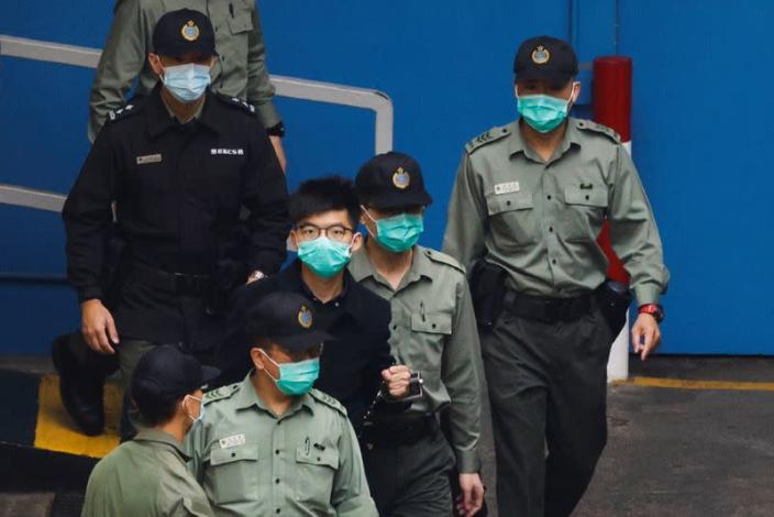 Pro-democracy activist Joshua Wong walks to a prison van to head to court with other activists, over a national security law charge, in Hong Kong
