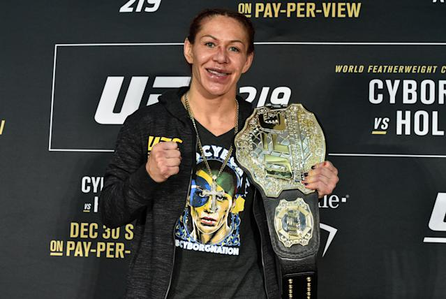 Cris Cyborg poses with her women's featherweight title belt after a hard-fought victory over Holly Holm on Saturday at T-Mobile Arena in Las Vegas. (Getty Images)