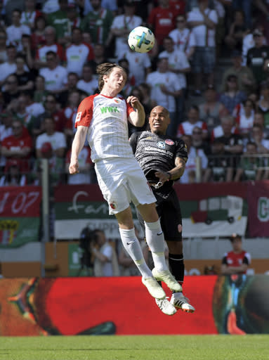 Augsburg's Michael Gregoritsch, left, and Mainz' Nigel de Jong challenge for the ball during the German Bundesliga soccer match between FC Augsburg and FSV Mainz 05, in Augsburg, Germany, Sunday, April 22, 2018. (Stefan Puchner/dpa via AP)