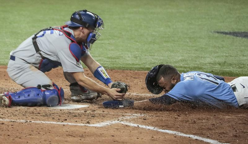 Tampa Bay Rays baserunner Manuel Margot is tagged out at the plate by Dodgers catcher Austin Barnes.