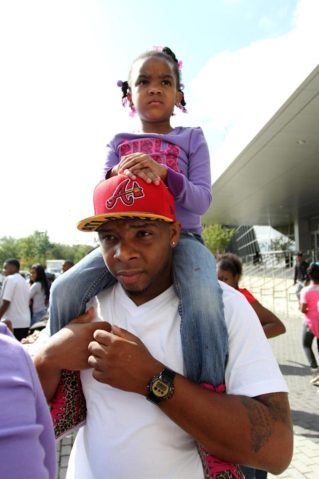 Jackson State fan Timothy Hudson and his daughter Rayland watch the homecoming parade, Saturday, Oct. 19, 2013, in Jackson, Miss. Jackson State decided to continue with homecoming festivities after Saturday's NCAA college football game against Grambling State was canceled because disgruntled Grambling players refused to travel to Jackson. (AP Photo/Charles Smith)