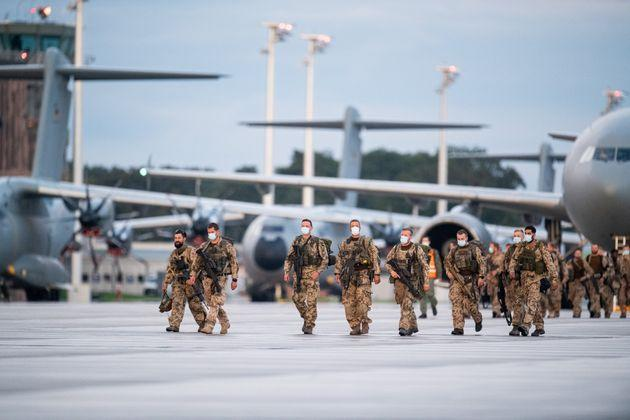 27 August 2021, Lower Saxony, Wunstorf: Soldiers disembark from the Bundeswehr's A400M transport aircraft and the Luftwaffe's Airbus A310 after landing at Wunstorf base in Lower Saxony. The first Bundeswehr soldiers have returned to Germany from their evacuation mission in Afghanistan. Three military planes landed at the Wunstorf airbase near Hanover shortly before 8:00 p.m. on Friday evening. An Airbus A310 of the German Air Force and two military transporters A400M were used for the return flight of the soldiers to Germany. The forces had taken off from Tashkent, the capital of Uzbekistan. The Bundeswehr had set up a hub there to fly Germans and threatened Afghans out of Kabul in short shuttle flights. Photo: Daniel Reinhardt/dpa (Photo by Daniel Reinhardt/picture alliance via Getty Images) (Photo: picture alliance via Getty Images)