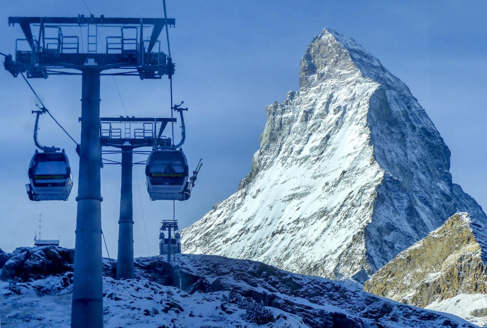 Gondolas go up next to the Matterhorn in Zermatt, Switzerland, Thursday, Dec.3, 2020. Zermatt is home to one of the Swiss ski stations that has become an epicenter of discord among Alpine neighbors. EU member states Austria, France, Germany and Italy are shutting or severely restricting access to the slopes this holiday season amid COVID-19 concerns, Switzerland is not. (AP Photo/Jamey Keaten)