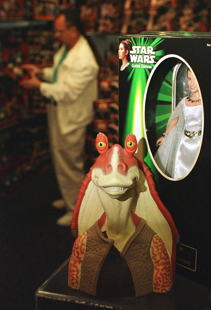 GARDEN CITY, : A figure of the character called Jar Jar Binks (C) from the new Star Wars movie The Phantom Menace sits next to a figure of Princess Leia (R) from the original Star Wars trilogy in a display at FAO Schwartz 07 May 1999 in Garden City, NY. FAO Schwartz filled an entire room with toys from both the new movie as well as the original series when the new figures were released 03 May 1999 . AFP PHOTO/Matt CAMPBELL (Photo credit should read MATT CAMPBELL/AFP via Getty Images)