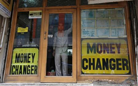 Two men look out from the glass door of a currency exchange shop in New Delhi