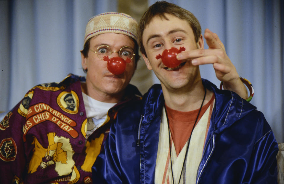 ENGLAND : Nicholas Lyndhurst and a guest show off the books sold for Red Nose Day 1991 in 1991 in England. (Photo by Mauro Carraro/Comic Relief via Getty Images)