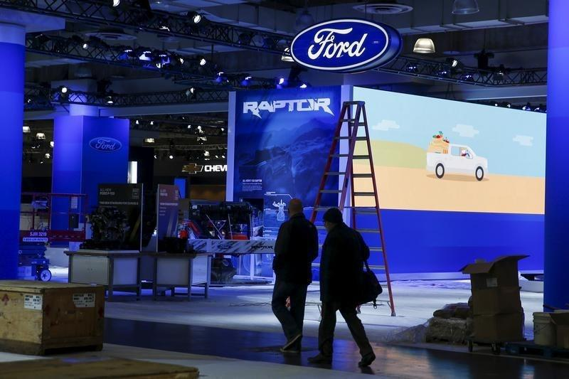 People walk near the Ford exhibit area of the New York International Auto Show at the Javits Center ahead of the event in New York