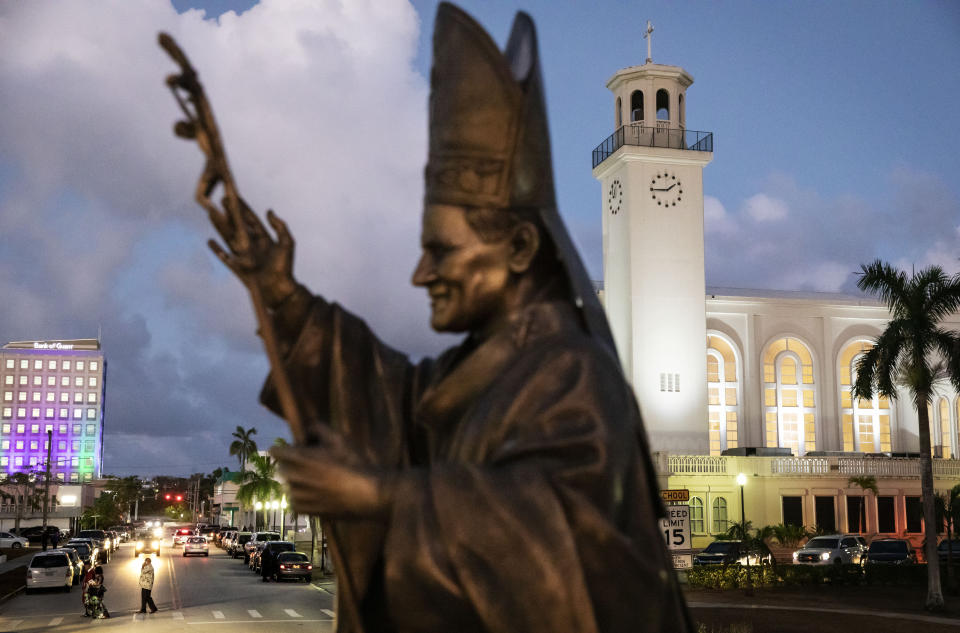 FILE - In this Tuesday, May 7, 2019 file photo, a statue of Pope John Paul II stands outside the island's main cathedral, Dulce Nombre de Maria Cathedral-Basilica, during a Mass in Hagatna, Guam. Over 200 clergy abuse lawsuits led church leaders in the U.S. territory to seek bankruptcy protection, as they estimated at least $45 million in liabilities. Even so, the Archdiocese of Agana's parishes, schools and other organizations have received at least $1.7 million in coronavirus rescue funds, even as it sues the Small Business Administration for approval to get a loan for its headquarters, according bankruptcy filings. (AP Photo/David Goldman)