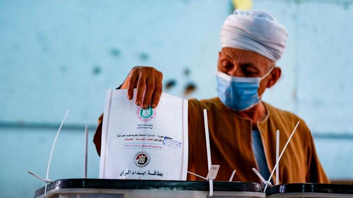 A man, mask-clad due to the COVID-19 coronavirus pandemic, casts his vote at a polling station in the Talibeya district of Giza, the twin-city of Egypt's capital, on October 24, 2020, while voting in the first stage of the lower house elections.