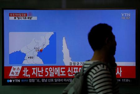 A passenger walks past a TV broadcasting a news report on North Korea's failed missile launch from its east coast, at a railway station in Seoul