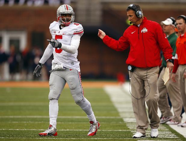 Ohio State head coach Urban Meyer, right, talks with his quarterback Braxton Miller, left, during the second half of an NCAA college football game against Illinois on Saturday, Nov. 16, 2013, in Champaign, Ill. Ohio State won the game 60-35. (AP Photo/Jeff Haynes)