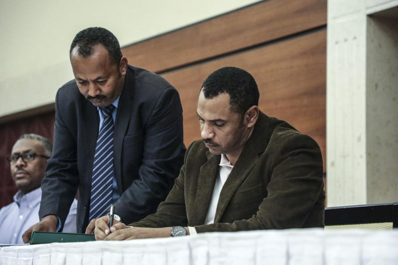 Sudan's pro-democracy movement leader Ahmad al-Rabiah signs a power sharing document with the ruling military council in Khartoum, Sudan, Wednesday, July 17, 2019. The two sides are still at work on a more contentious constitutional agreement that would specify the division of powers. (AP Photo/Mahmoud Hjaj)