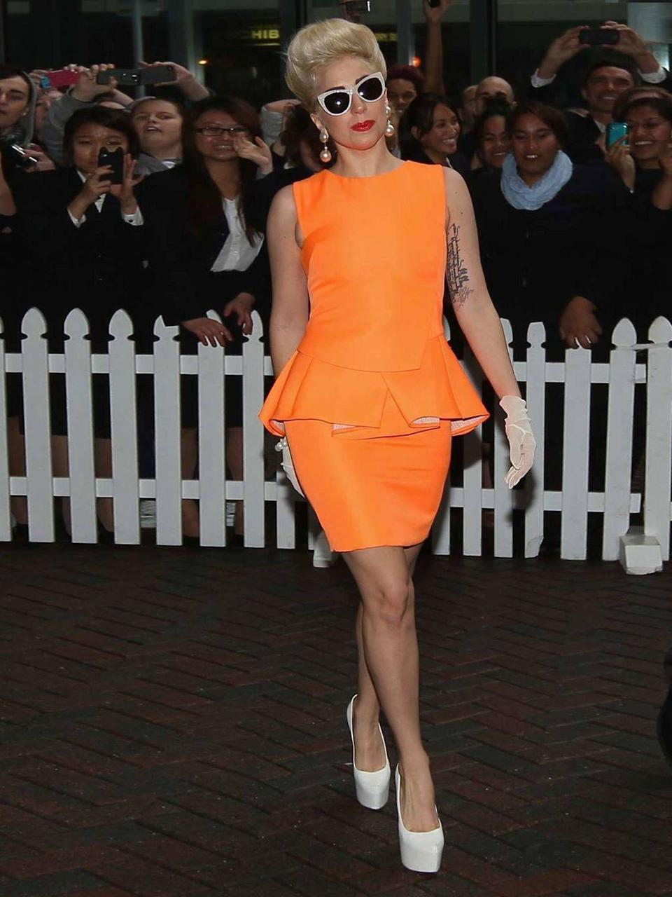 <p>Lady Gaga arrives at the Stamford Plaza wearing an orange peplum dress paired with white heels, June 2012.</p>