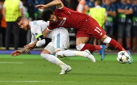 Salah injures his shoulder when Ramos challenges him, holds on to his arm then pins him to the ground - Credit: GENYA SAVILOV/AFP/Getty Images