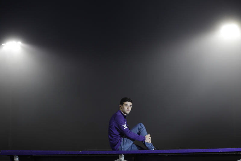 """Dan Afflitto, a senior at Rumson-Fair Haven Regional High School, poses for a picture in front of the floodlights that light up the football field at his school in Rumson, N.J., on May 22, 2020. The school has been turning on the football field lights for 20 minutes every Friday night to honor the class of 2020. Dan, who graduates June 19, lost his father, for whom he is named, in the terror attacks of Sept. 11, 2001 -- months before the younger Dan was born. He said he often thought of his dad during the national anthem before his football and basketball games. """"It just made me want to play the best that I could,"""" he says. (AP Photo/Seth Wenig)"""