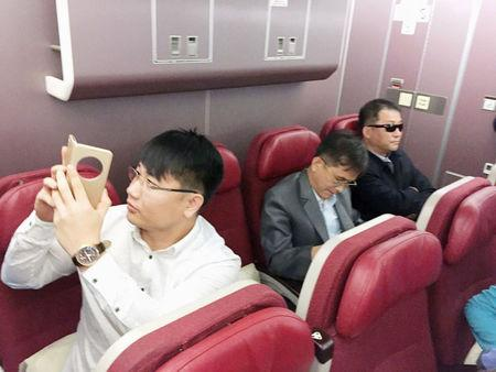 Passengers believed to be North Koreans including Kim Uk Il (L) are seen inside an airplane for the flight bound for Beijing, at an airport in Kuala Lumpur in Malaysia, in this photo taken by Kyodo March 30, 2017. Mandatory credit Kyodo/via REUTERS