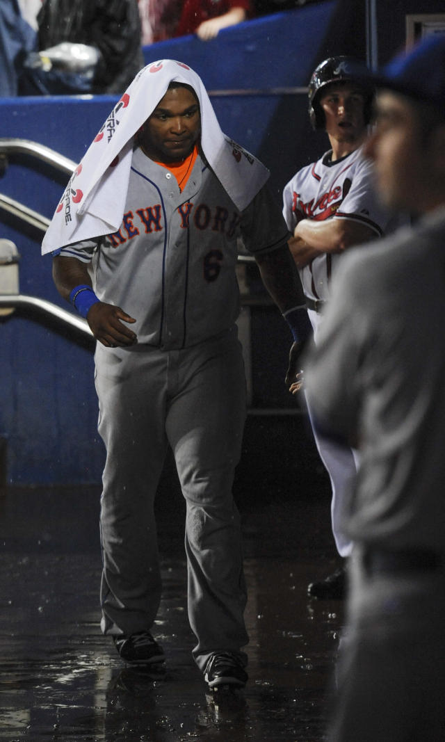 New York Mets' Marlon Byrd tries to stay dry with a towel while waiting out a rain delayed start before facing the Atlanta Braves during a baseball game, Monday, June 17, 2013, in Atlanta. (AP Photo/John Amis)