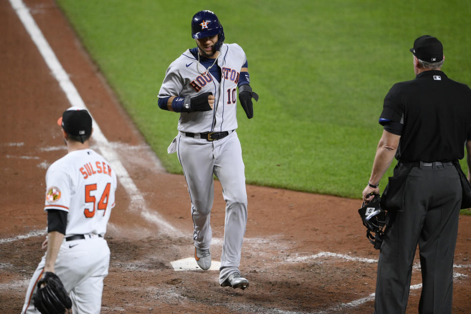 Houston Astros' Yuli Gurriel (10) scores a run on a sacrifice fly by Chas McCormick, not seen, during the eighth inning of a baseball game, Tuesday, June 22, 2021, in Baltimore. Baltimore Orioles relief pitcher Cole Sulser is at left. The Astros won 3-1. (AP Photo/Nick Wass)