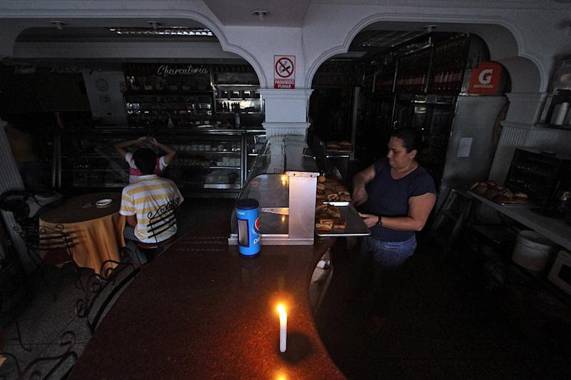 A woman works in candlelight at a bakery during a power cut in the border state of San Cristobal on April 25, 2016