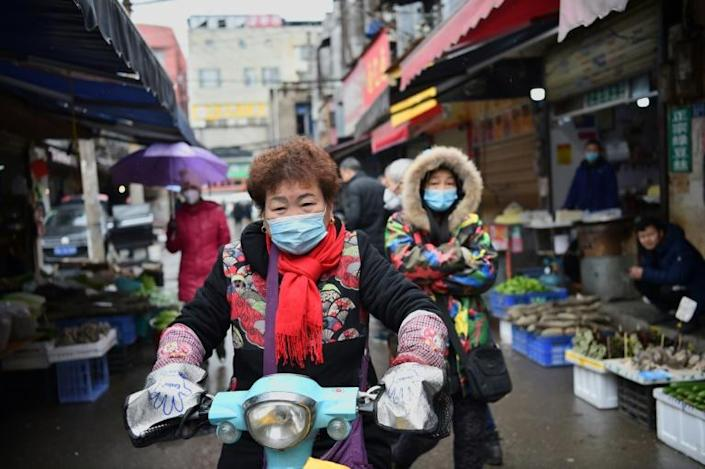 Artificial intelligence systems picked up early clues about the coronavirus outbreak by scanning news images and social media posts from a market in Wuhan, China, where the first cases were detected (AFP Photo/HECTOR RETAMAL )