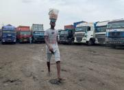 An egg-seller walks past food supply trucks parked at a garage in Lagos