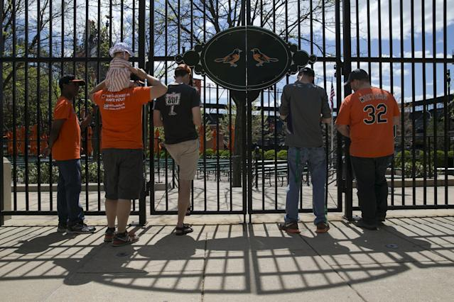 Fans sit outside Camden Yards ballpark before the start of the Baltimore Orioles against Chicago White Sox America League baseball game in Baltimore, Maryland April 29, 2015. In what will be a first for Major League Baseball, the Baltimore Orioles will host the Chicago White Sox on Wednesday in a stadium closed to fans as Baltimore copes with some of the worst U.S. urban rioting in years.REUTERS/Shannon Stapleton