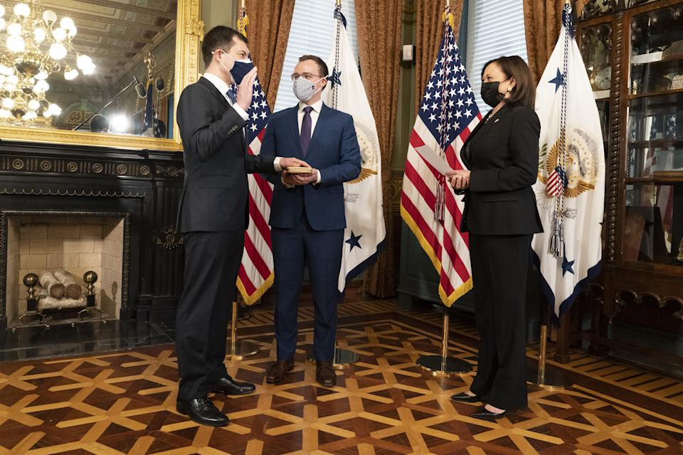 U.S. Vice President Kamala Harris, right, swears in Pete Buttigieg, U.S. secretary of transportation, left, during a ceremony with husband Chasten Buttigieg, center, in Washington, D.C., U.S., on Feb. 3, 2021. (Chris Kleponis/CNP/Bloomberg via Getty Images)