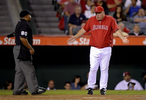 Los Angeles Angels manager Mike Scioscia, right, argues with home plate umpire Adrian Johnson after Seattle Mariners' Trayvon Robinson struck out swinging, but was called safe at first when the ball was dropped and thrown to first hitting Robinson during the fourth inning of their baseball game, Tuesday, Sept. 25, 2012, in Anaheim, Calif. (AP Photo/Mark J. Terrill)