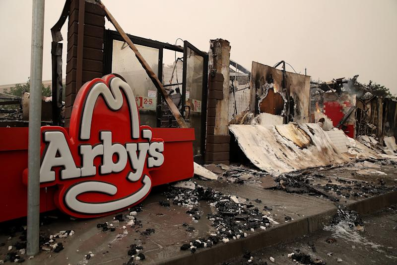 A sign sits on the ground next to a fire damaged Arby's restaurant in Santa Rosa.