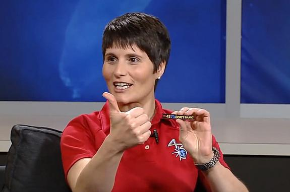 """International Space Station Expedition 42 flight engineer Samantha Cristoforetti holds out her thumb, mimicking the hand on her """"Don't Panic"""" patch, inspired by """"The Hitchhiker's Guide to the Galaxy."""""""