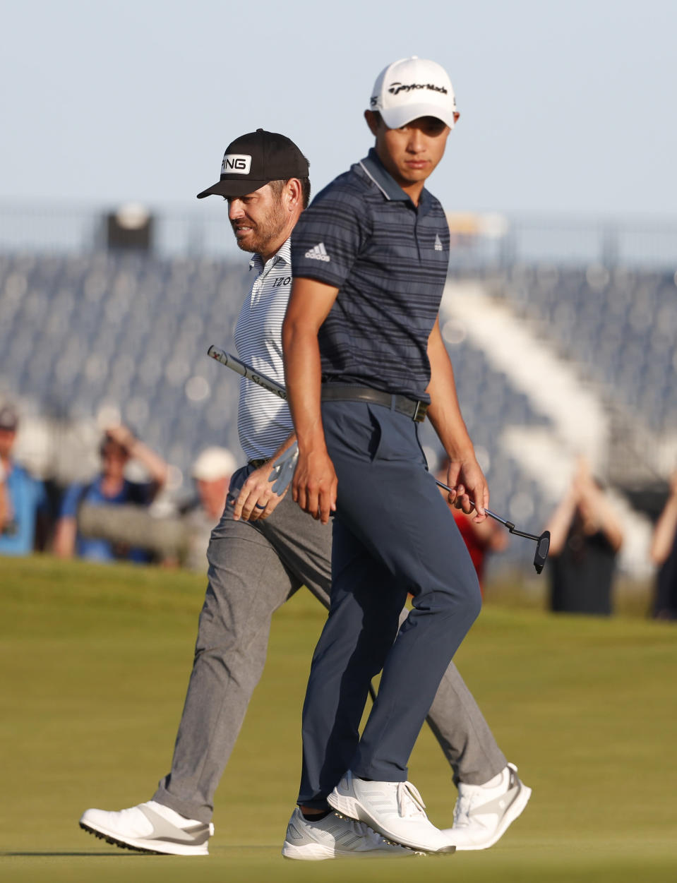 South Africa's Louis Oosthuizen, rear walks on the 17th green as tUnited States' Collin Morikawa, passes during the third round of the British Open Golf Championship at Royal St George's golf course Sandwich, England, Saturday, July 17, 2021. (AP Photo/Peter Morrison)
