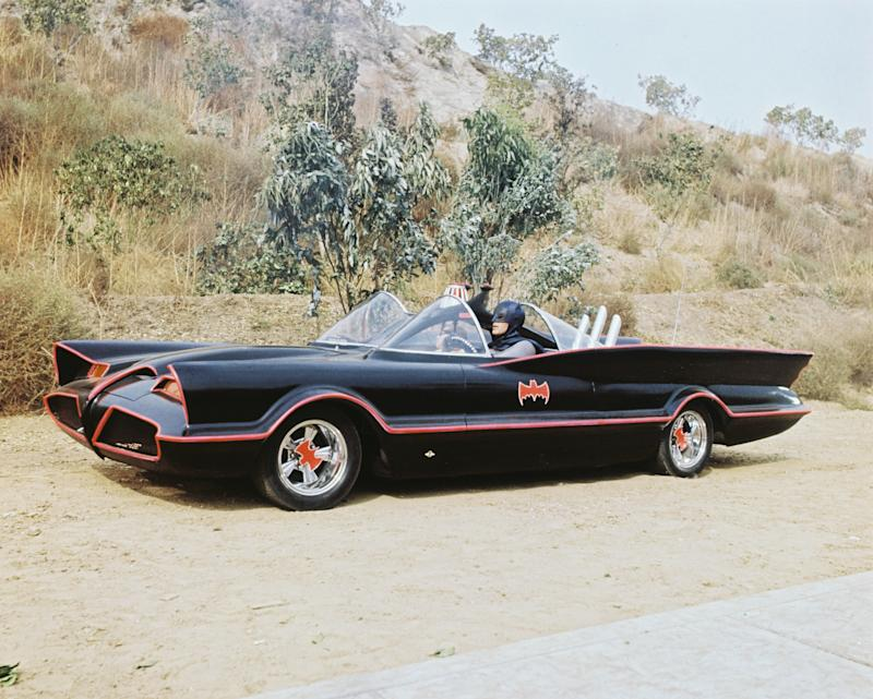 American actor Adam West as Bruce Wayne/Batman at the wheel of the Batmobile with passenger Burt Ward as Dick Grayson/Robin in the TV series 'Batman', circa 1966. The Batmobile was a modified version of the 1955 Lincoln Futura concept car. (Photo by Silver Screen Collection/Hulton Archive/Getty Images)
