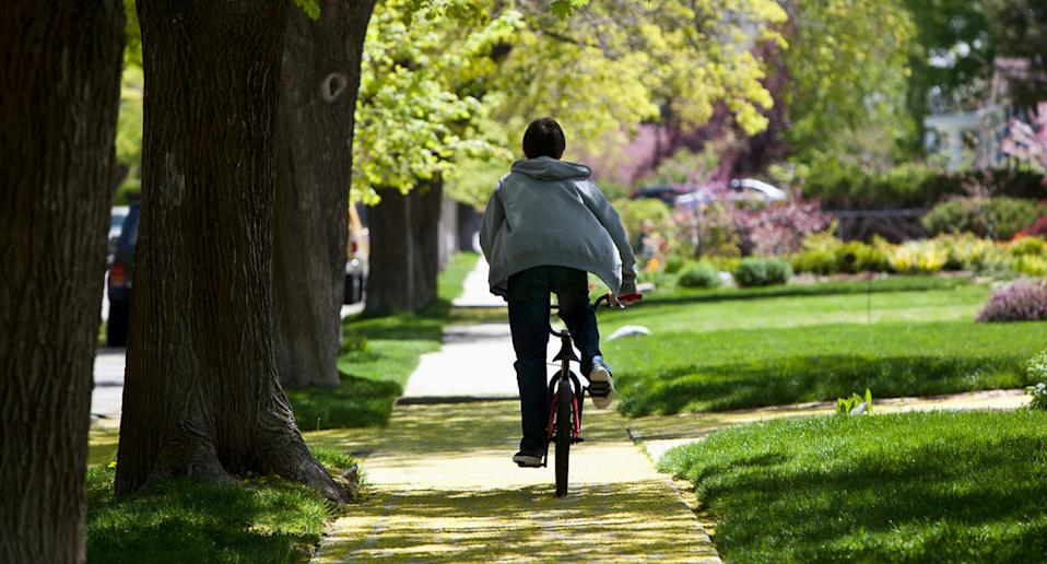 Stock image of a boy riding a bike without a helmet.