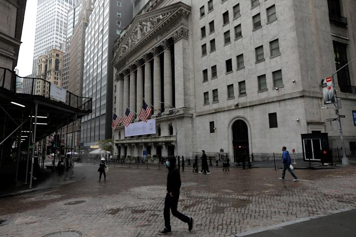 People wearing protective face masks walk outside the New York Stock Exchange in Manhattan in New York City, New York, U.S., October 26, 2020. REUTERS/Mike Segar