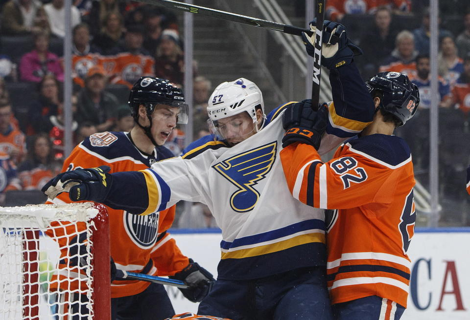 St. Louis Blues' David Perron (57) is roughed up by Edmonton Oilers' Ryan Nugent-Hopkins (93) and Caleb Jones (82) during the first period of an NHL hockey game, Tuesday, Dec. 18, 2018 in Edmonton, Alberta. (Jason Franson/The Canadian Press via AP)
