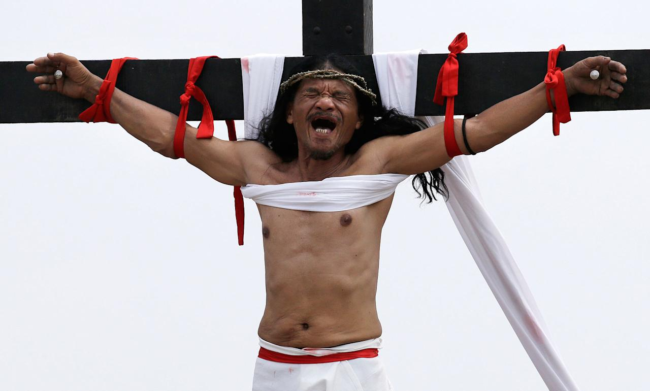 <p>Ruben Enaje grimaces after gets nailed to the cross for the 32nd year in a row during a reenactment of Jesus Christ's sufferings as part of Good Friday rituals in the village of San Pedro Cutud, Pampanga province, northern Philippines March 30, 2018. Thousands of Filipino Roman Catholic devotees and tourists descended Friday on a farming village north of Manila to witness the crucifixion of several men in a reenactment of Jesus Christ's sufferings, a gory annual tradition church leaders frown upon. (Photo: Aaron Favila/AP) </p>