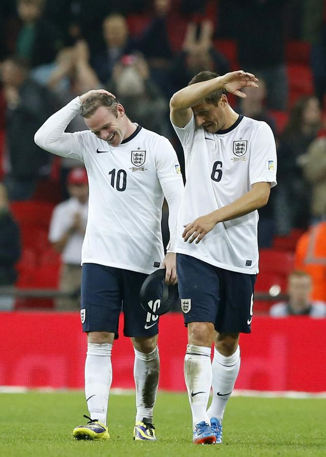 England's Wayne Rooney, left, and Phil Jagielka gesture after the World Cup Group H qualification soccer match between England and Poland at Wembley stadium in London, Tuesday, Oct. 15, 2013. England won the match 2-0 and qualify for the 2014 World Cup in Brazil. (AP Photo/Matt Dunham)