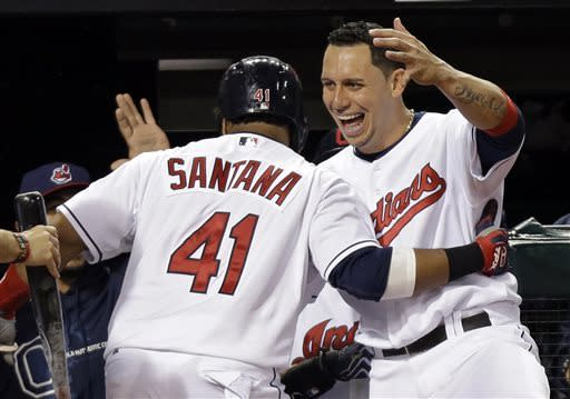 Cleveland Indians' Asdrubal Cabrera hugs Carlos Santana (41) after Santana's solo home run against the Oakland Athletics in the sixth inning of a baseball game Wednesday, May 8, 2013, in Cleveland. (AP Photo/Mark Duncan)