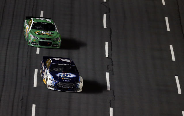 Brad Keselowski (2) drives past Kasey Kahne (5) during the NASCAR Sprint Cup Series auto race at Charlotte Motor Speedway in Concord, N.C., Saturday, Oct. 12, 2013. (AP Photo/Chris Keane)