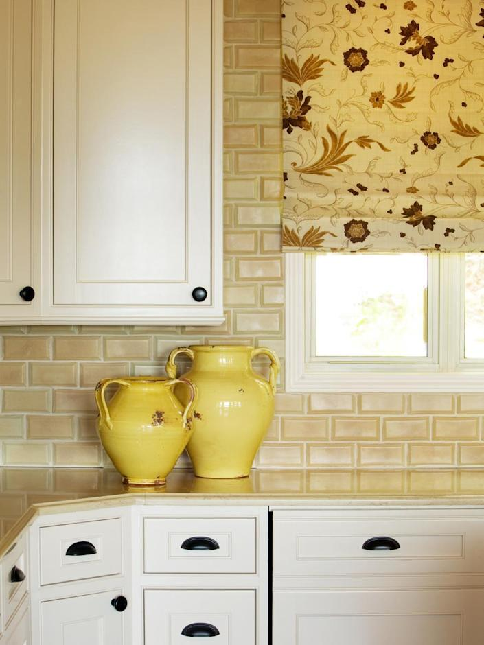 """<p>To liven up a basic backsplash, consider a beveled tile. """"Having the tile done this way added a lot of dimension to the walls,"""" explains designer Tobi Farley. """"It adds texture to the neutral kitchen, and the varying shades of bisque and sand complement the Roman shade perfectly. I love working with tile in new and different ways – it can really add to a design!""""</p>"""