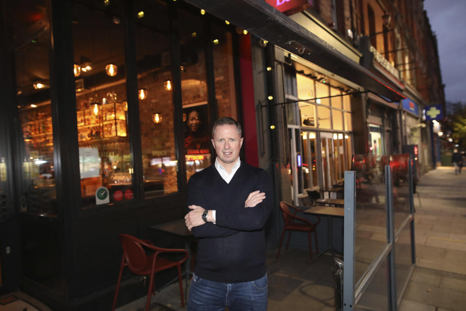Paul Cadden, owner of the Saba restaurant group poses for a photograph in his restaurant in Dublin, Ireland, Wednesday, Oct. 21, 2020. Paul Cadden will have to lay off 20 people, but will do whatever is necessary to get through lockdown. With COVID-19 cases on the rise, the government has imposed a tough new lockdown, shutting down non-essential shops, limiting restaurants to takeout service and ordering people to stay within five kilometers (three miles) of their homes for the next six weeks. (AP Photo/Peter Morrison)